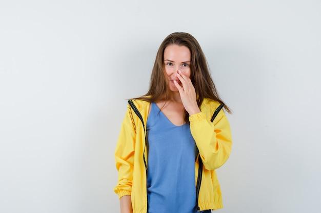Молодая дама в футболке позирует, касаясь ее носа и выглядя заманчиво