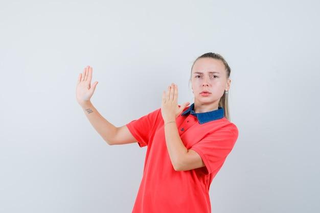 가라테 절단 제스처를 표시하고 엄격한 찾고 t- 셔츠에 젊은 아가씨