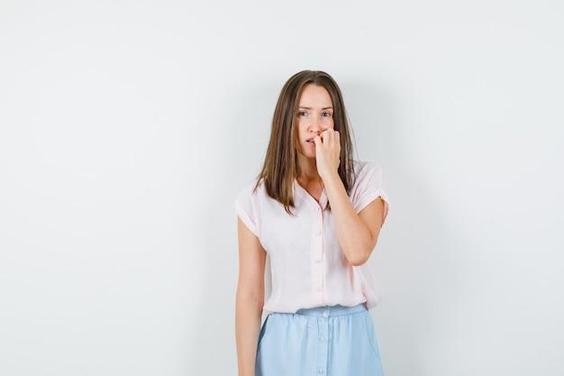 T- 셔츠에 젊은 아가씨, 손톱을 물어 뜯는 치마와 잠겨있는, 전면보기를 찾고.
