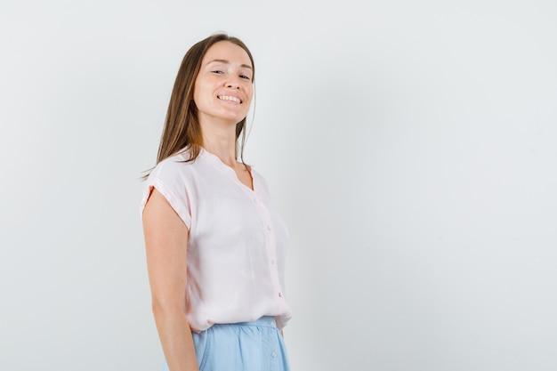 Молодая дама в футболке, юбке смотрит в камеру и выглядит веселой, вид спереди.