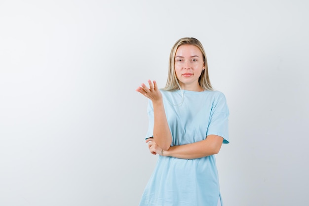 제스처를 심문하고 꽤 고립 된 찾고 t- 셔츠에 젊은 아가씨 손을 스트레칭