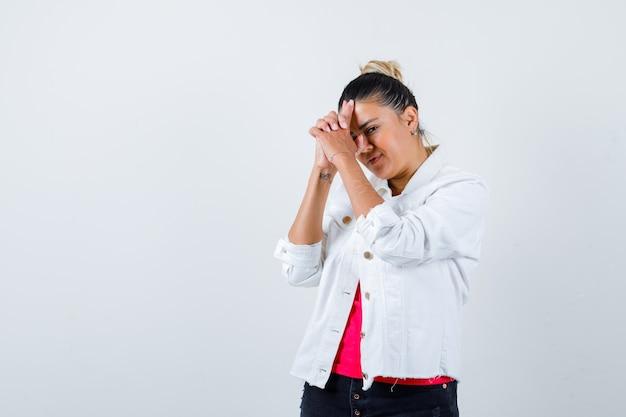 Tシャツを着た若い女性、頭に銃のジェスチャーを示し、自信を持って見える白いジャケット、正面図。