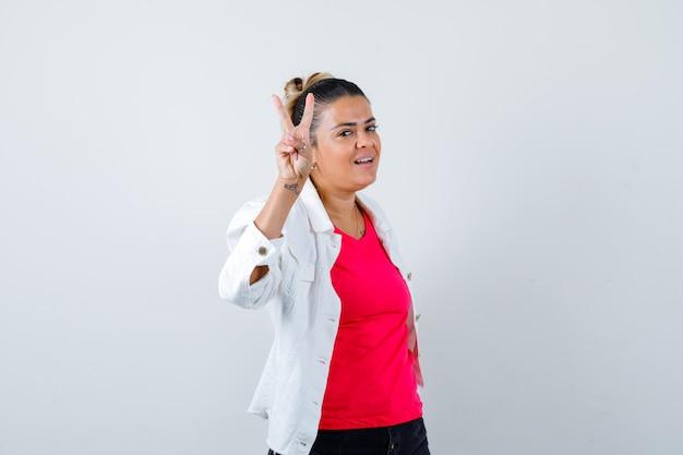 Молодая дама в футболке, белой куртке показывает знак победы и радостно смотрит, вид спереди.