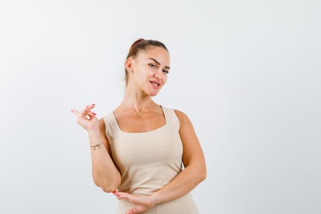 タンクトップの若い女性が後ろを向いて自信を持って、正面図。