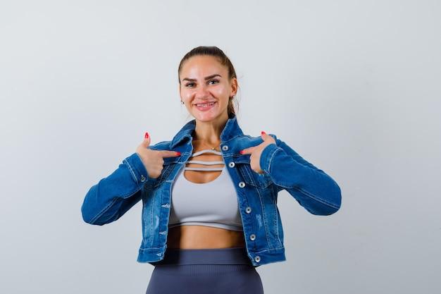 上に若い女性、自分を指して嬉しそうに見えるデニムジャケット、正面図。