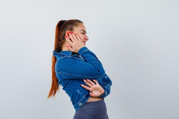 上に若い女性、頬に手と陽気に見えるデニムジャケット、正面図。
