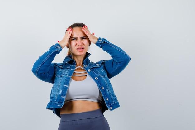 上に若い女性、額に手を置いて気になるデニムジャケット、正面図。