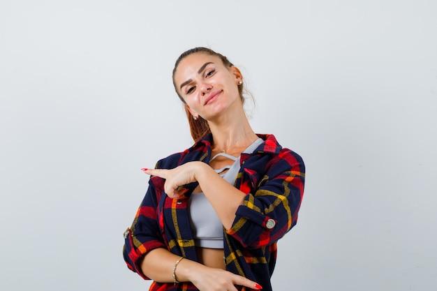 上に若い女性、左側を指して自信を持って見える格子縞のシャツ、正面図。