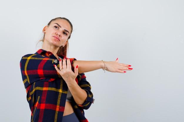 Молодая дама в верхней части, клетчатой рубашке протягивает руку, держа ее за руку и смотрит задумчиво, вид спереди.