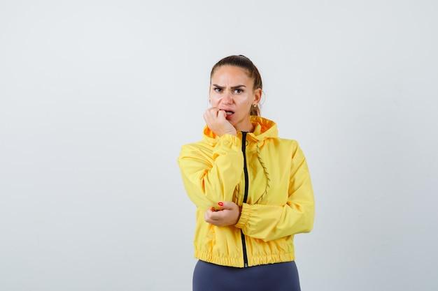 운동복을 입은 젊은 여성이 인상을 찡그리며 불안해하면서 감정적으로 손톱을 물어뜯고 있습니다.