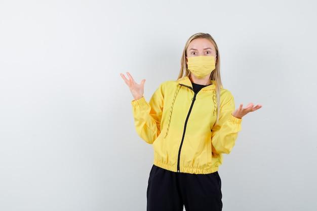 トラックスーツを着た若い女性、手のひらを脇に広げて困惑しているように見えるマスク、正面図。