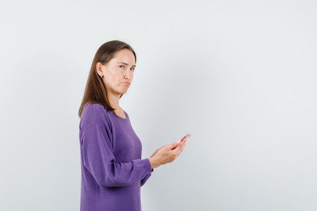 Молодая дама в фиолетовой рубашке держит мобильный телефон и смотрит задумчиво.