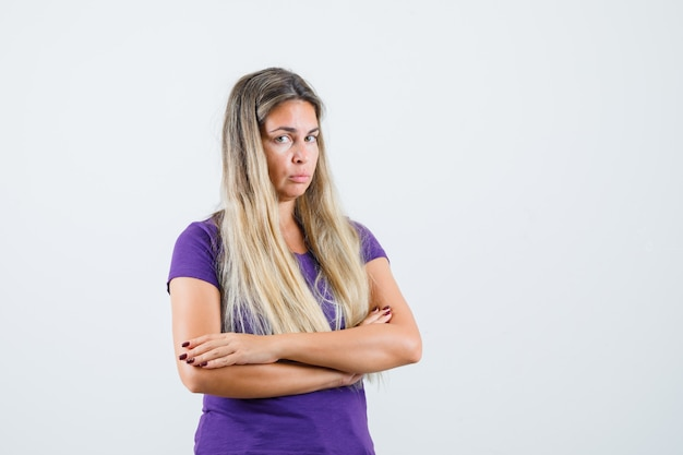 腕を組んで立って、悲しそうに見える紫のtシャツの若い女性、正面図。
