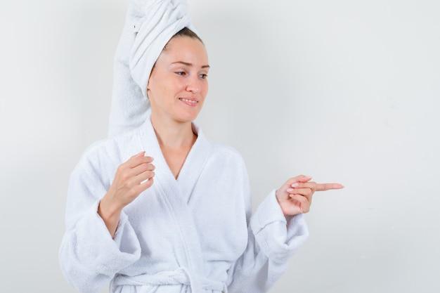 白いバスローブを着た若い女性、右側を向いて陽気に見えるタオル、正面図。