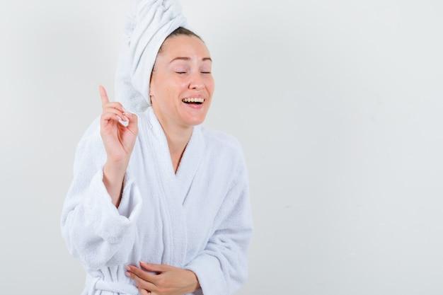 흰색 목욕 가운, 수건을 가리키고 행복, 전면보기를 찾고있는 젊은 아가씨.