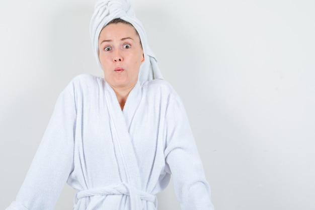Молодая дама в белом халате, полотенце, показывающем жест сомнения и озадаченном, вид спереди.