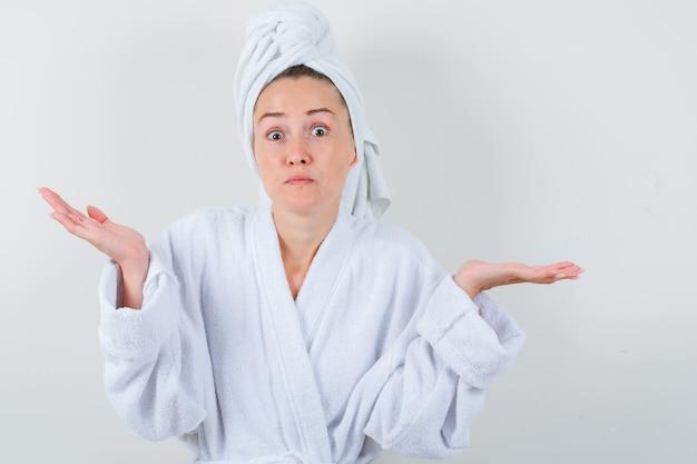 Молодая дама в белом халате, полотенце показывает жест сомнения и выглядит озадаченным, вид спереди.