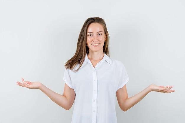 미소하고 기쁘게 보는 동안 팔을 여는 흰 블라우스에 젊은 아가씨