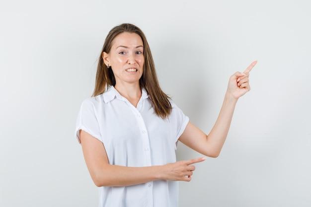 Молодая дама в белой блузке указывает в сторону и скучает