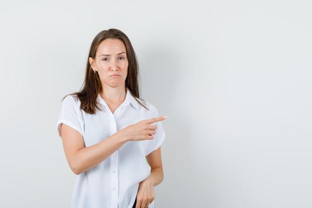 Девушка в белой блузке, указывая в сторону