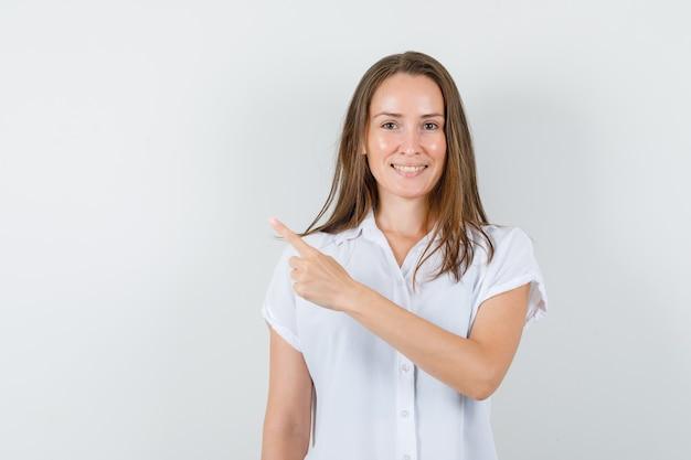 Молодая дама в белой блузке показывает вправо и радостно смотрит