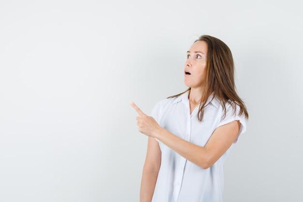 白いブラウスを着た若い女性が向きを変えて好奇心旺盛に見える