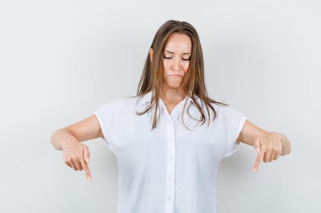 白いブラウスを着た若い女性が下を向いてストレスを感じている