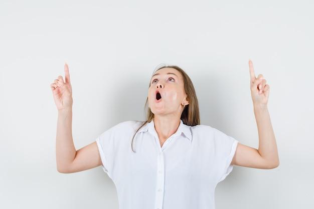 Молодая дама в белой блузке, указывая вверх и выглядя шокированной