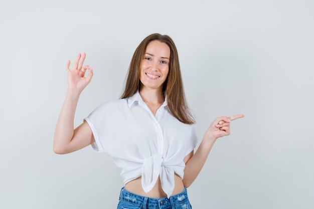 옆으로 가리키고 긍정적 인, 전면보기를 보면서 확인 제스처를 보여주는 흰 블라우스에 젊은 아가씨.