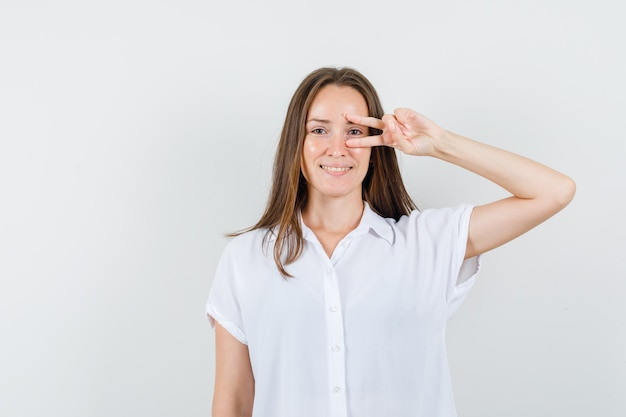 Молодая дама в белой блузке показывает жест победителя на глазах и хорошо выглядит