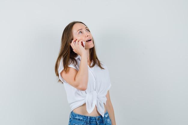 Молодая дама в белой блузке разговаривает по телефону и смотрит сосредоточенно, вид спереди.