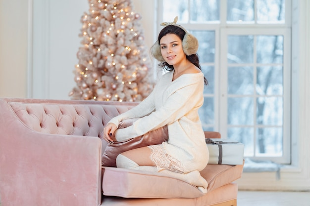 크리스마스 시간에 소파에 하얀 드레스를 입고 젊은 아가씨