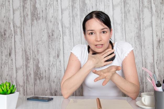 灰色の壁に黒のイヤホンで彼女の手で感情を示す白いシャツの若い女性