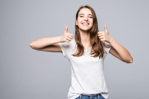 白いtシャツとジーパンの若い女性は白いスタジオ背景の前で歌う親指を示しています