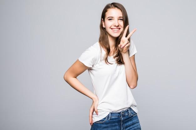 白いtシャツとジーパンの若い女性は白いスタジオ背景の前で勝利のサインを示しています
