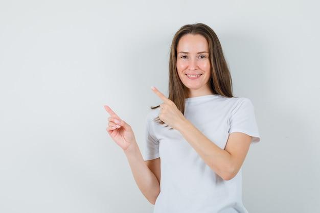 Молодая дама в белой футболке, указывающая в левый верхний угол и уверенная в себе