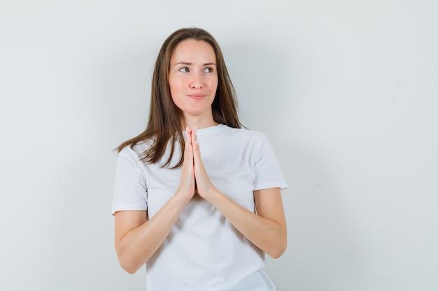 ナマステのジェスチャーを示し、希望に満ちた白いtシャツの若い女性