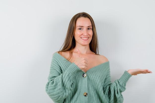 親指を上に向けて歓迎のジェスチャーを示し、陽気に見えるウールのカーディガンの若い女性、正面図。