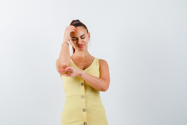 頭に手をつないで、ダウンキャスト、正面図を見て黄色のドレスの若い女性。