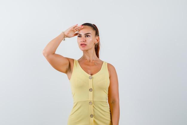 黄色いドレスを着た若い女性が頭を抱えて遠くを見て、不思議に思っている、正面図。