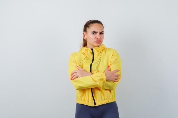 노란색 재킷을 입은 젊은 여성이 자신을 껴안고 춥고 우울해 보이는 전면 전망.