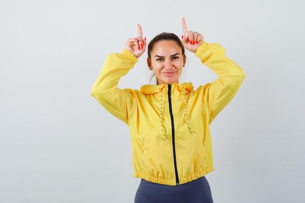 雄牛の角のように頭の上に指を持ち、面白がって見える黄色いジャケットの若い女性、正面図。