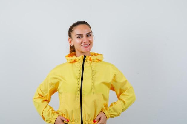 腰に手と楽観的な、正面図を探している黄色のジャケットの若い女性。