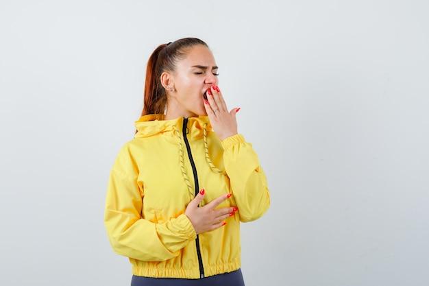 黄色いジャケットの若い女性が口に手を当てて、眠そうな顔をしてあくびをしている、正面図。