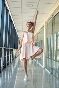 ピンクの魅力的なドレスでポーズをとって長い廊下の中の若い女性