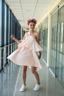 Young lady inside long corridor posing in pink glamour dress