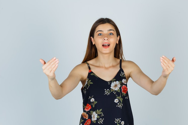 Giovane donna che invita a entrare in camicetta e sembra felice, vista frontale.