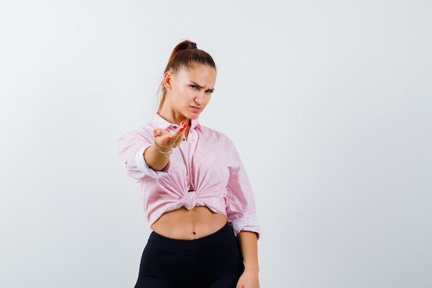 Young lady inviting to come in shirt, pants and looking serious. front view.
