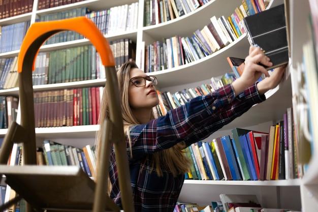 若い女性は多くの本の中から適切な文学を探しています