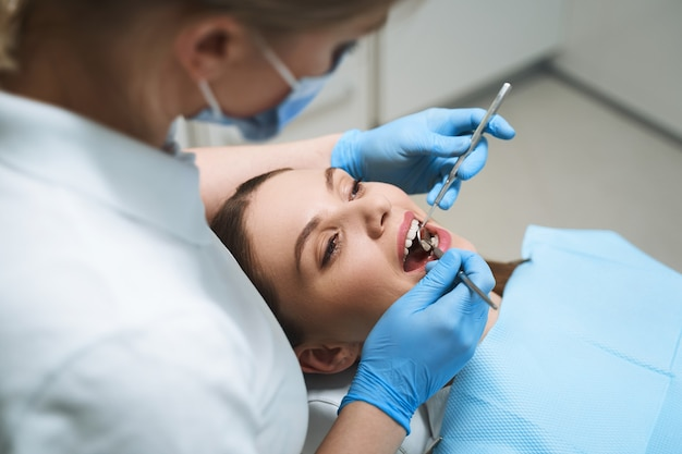 Молодая женщина лежит в стоматологическом кресле, пока женщина-врач использует инструменты для обследования
